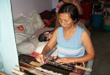 A refugee at a hand loom in Delhi. © Burma Center Prague